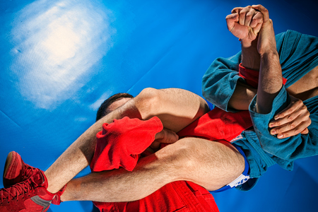 Two wrestlers of grappling and jiu jitsu in a blue and red kimono makes armlock on blue tatami. Close-up Wrestler submission wrestling