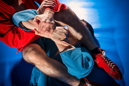 Close-up two wrestlers of grappling and jiu jitsu in a blue and red kimono makes armlock. Wrestler submission wrestling  blue tatami