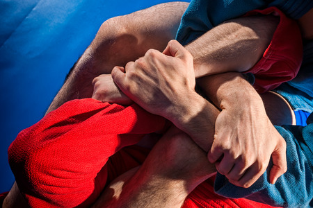 Man wrestlers of grappling and jiu jitsu in a blue and red kimono makes submission wrestling. Fighting techniques:; armbar; armlock Stock Photo
