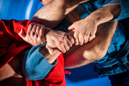 Close-up two wrestlers of sambo and jiu jitsu in a blue and red kimono doing . Man wrestler makes submission wrestling or armbar on blue tatami Stock Photo