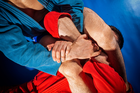 Man wrestler of sambo and jiu jitsu in a blue and red kimono doing makes submission wrestling or armbar on blue ground.Fighting techniques:   armbar, armlock Stock Photo