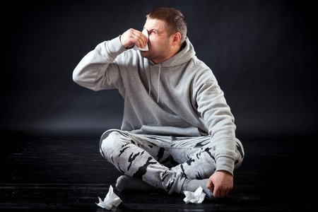 A young sad man in sports clothes is sitting on the floor sick, holding a napkin in his hand and blowing his nose on a black isolated background. The man sneezes