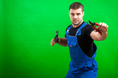 A dark-haired male builder in a black T-shirt and blue construction jumpsuit is holding a secateur and scissors on metal on a green isolated background