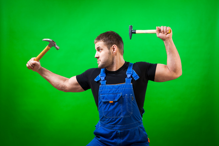 A dark-haired male construction worker wearing a black T-shirt and blue construction overall having fun, laughing funny and  holding two wood hammer  on a green isolated background