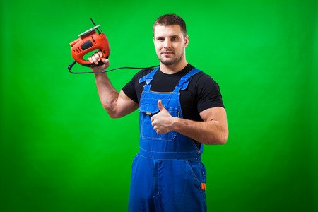 A dark-haired male construction worker in a black T-shirt and blue construction overall holds in hands a red hand tool Jjg saw or bare tool on a green isolated background