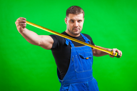 A young male carpenter wearing a black T-shirt and blue construction jumpsuit shows a long yellow tape rule for construction work on a green isolated background