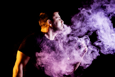 The man smoke an electronic cigarette on the dark background Stock Photo