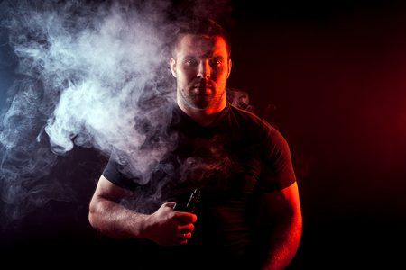 A young stylish man smoker in a black T-shirt is holding a    vape in his hand, and around and a big cloud of smoke from vape on a dark isolated background