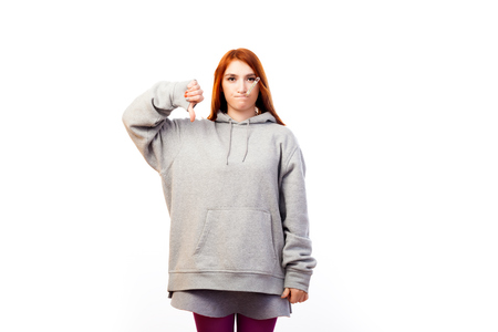 A young red-haired woman in a sports sweatshirt is sad, from being ill and measuring the temperature by a thermometer on a white isolated background Stok Fotoğraf