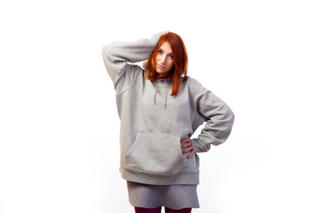 A young red-haired woman in a gray sweatshirt suffers a headache, but smiles and holds herself by the hand behind the head on a white isolated background Stock Photo