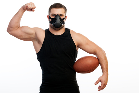 A young athletic man  sportsman in a sports T-shirt, training black mask show biceps and holds in his hand a rugby ball   on white  isolated background