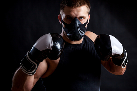 Portrait of young athletic man wearing  sport shirt, training mask and  boxing gloves on black isolated background