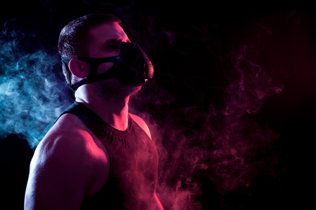 A young athletic man in a sports shirt breathes through a training black mask around a blue and red smoke cloud from a vape on a black isolated background Banco de Imagens