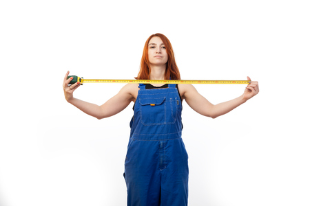 A young red-haired woman in a black T-shirt and blue construction overall holds an type rule on a white isolated background 写真素材