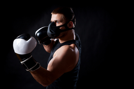A dark-haired male athlete in a black training mask, sports shirt and black and white boxing gloves boxing on a black isolated background Фото со стока