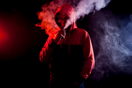 The man smoke an electric cigarette on the bright light background