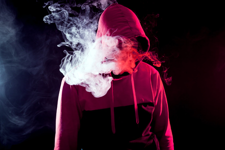 The man in the hood smoke an electronic cigarette  on a background of white smoke