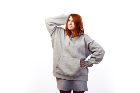 A young red-haired woman in a gray sweatshirt is pensive and holds on to her head with one hand on a white isolated background