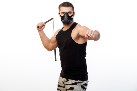 A young sporty blue-eyed man in a sporty black T-shirt, wearing boxing gloves and a black training mask is holding a metal nunchak in his hand on a white isolated background Stock Photo