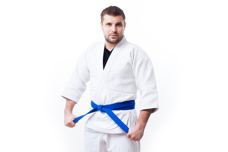 Young sporty man with dark hair in a white kimono with blue sambo belt, jiu jitsu, judo stands and keeps his hands on a white isolated background, front view