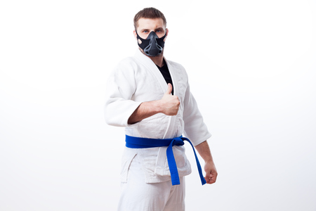 Young man fighter in a white kimono with blue belt for judo, jujitsu, black training mask pose  and holds the thumb up on isolated white background