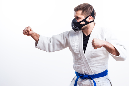 A young athletic man is a fighter in a white kimono for judo, jiu jitsu, sambo with a blue belt standing in a fighting rack on a white isolated background Stock Photo