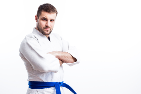 Young sporty man with dark hair in a white kimono with blue belt for sambo, jiu jitsu, judo stands with his arms crossed on a white isolated background Stock Photo