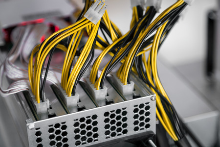 Close-up of cryptocurrency mining: cable, yelllow lights