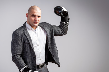 A young bald man in a white shirt, gray suit and boxing gloves seriously looks into the camera, shows a biceps and poses on a white isolated background