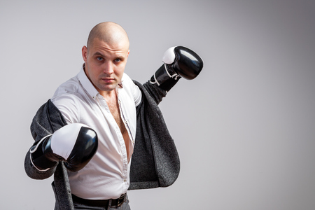 Bald man, confident manager in an unbuttoned white shirt, gray suit and boxing gloves posing and boxing on a white isolated background, front view