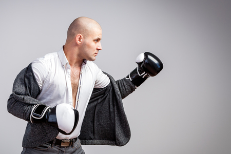 Bald man, confident manager in an unbuttoned white shirt, gray suit and boxing gloves box on a white isolated background, side view Stockfoto