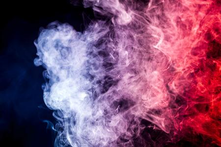 Colorful  red and blue  smoke clouds on dark background.Background of smoke vape Фото со стока