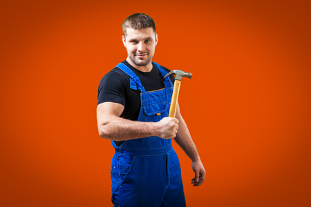 A dark-haired male construction worker in a black T-shirt and blue construction overalls beautifully posing and holding in his hand   wood hammer on a orange isolated background Stock Photo