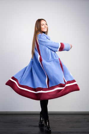 Young dark-haired woman in blue fur coat made from natural mink fur with claret-colored white stripes is relaxed, posing and dancing on white isolated background