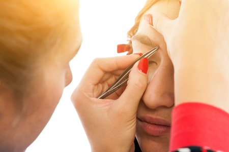 Close-up make-up artist plucks his eyebrows with a metal tweezers to a young red-haired woman