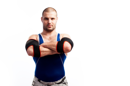 Young sportive man in blue tights and black elbow stands and holds his hands cross-over on his chest on a white isolated background