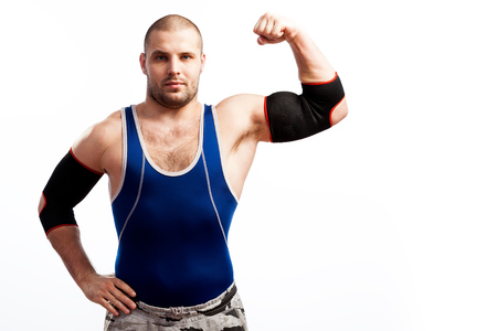 Young athletic man in blue tights and black elbow stands and shows biceps on white isolated background