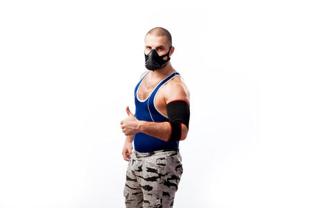 Young sportive man in blue tights,black elbow  and trainig mask stands and shows thumb up on a white isolated background