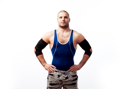 Young sportive man in blue tights and black elbow stands on a white isolated background Stock Photo