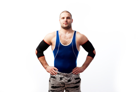 Young athletic male wrestler in blue shirt, sport pants and elbow pads standing with hands on waist on white isolated background