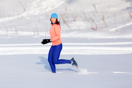 A young woman in a bright blue hat, an orange sweatshirt and elk skirts runs through the winter snow on a bright winter day, a side view Zdjęcie Seryjne