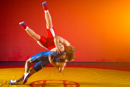 Two greco-roman  wrestlers in red and blue uniform wrestling  on a yellow wrestling carpet in the gym