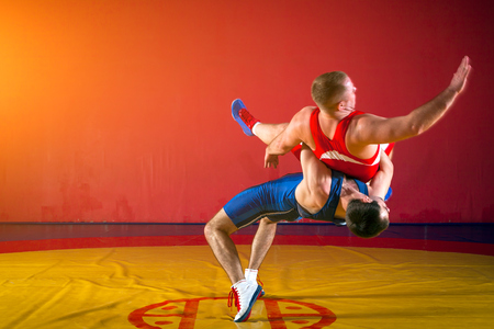 Two greco-roman  wrestlers in red and blue uniform making a suplex wrestling   on a yellow wrestling carpet in the gym