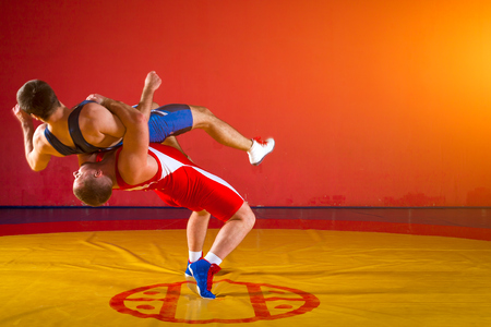 Two greco-roman  wrestlers in red and blue uniform making a suplex wrestling  on a yellow wrestling carpet in the gym Stock Photo