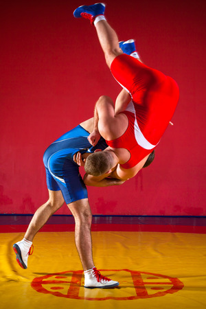 Two greco-roman  wrestlers in red and blue uniform making a suplex wrestling  on a yellow wrestling carpet in the gym Foto de archivo