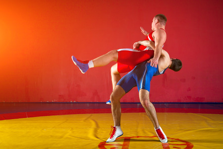 Two greco-roman  wrestlers in red and blue uniform wrestling   on a yellow wrestling carpet in the gym Фото со стока - 95519673