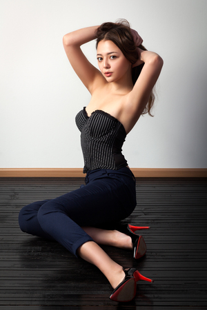 Asian young woman  in black top and classic black pants posing and sitting on a  black wooden floor against a white wall background