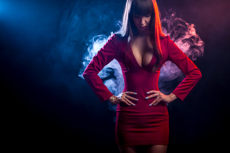 Young dark-haired woman in a red dress posing against a background of red and  blue smoke from a vape on a black isolated background Archivio Fotografico