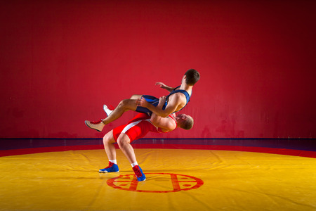Two strong wrestlers in blue and red wrestling tights are wrestlng and making a  hip throw wrestling on a yellow wrestling carpet in the gym. Young man doing grapple. Stock Photo