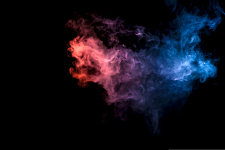 Dense multicolored smoke of blue, red on a black isolated background. Background of smoke vape